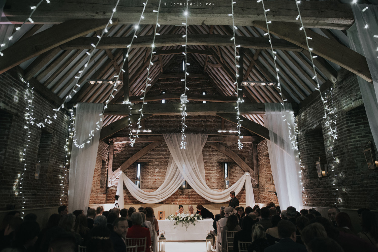 Barn wedding decor with fairy light canopy and drape