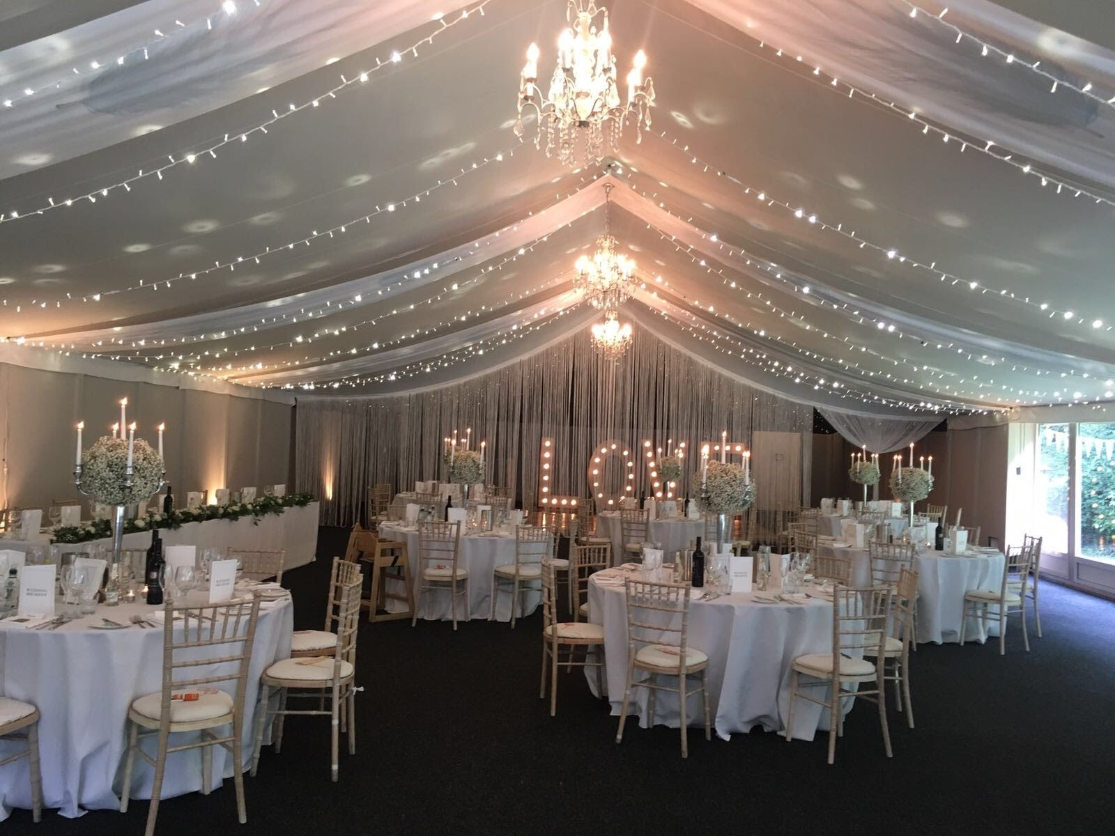 Thrumpton Hall wedding decor with ceiling drape and fairy light canopy ceiling installation and light up love letters