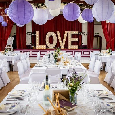 Village Hall wedding decor with radial fairy light ceiling canopy, paper lanterns and illuminated love letters.