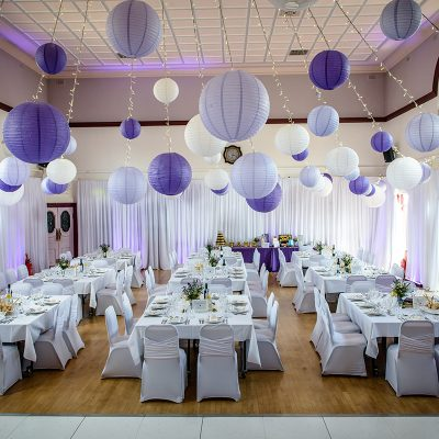 Village Hall wedding decor with radial fairy light ceiling canopy, paper lanterns, wall drapes and LED starlit dance floor.