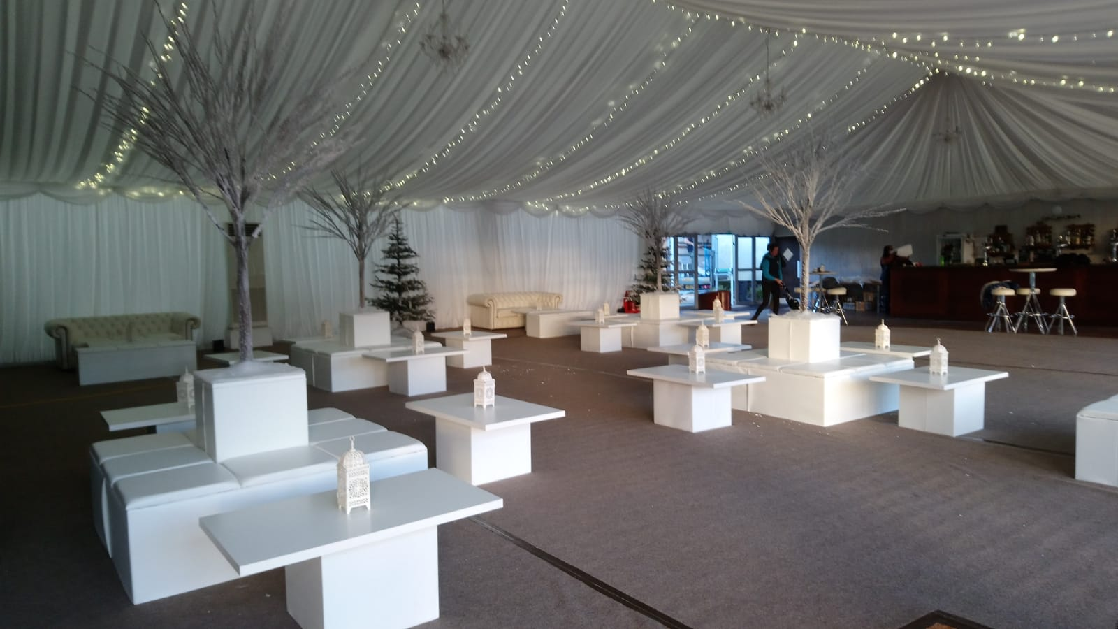 Grange Farm winter wedding decor hire with white furniture, fairy light canopy ceiling installation and frozen trees