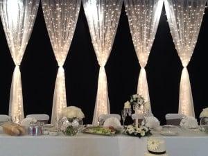 gathered fairy light curtain head table backdrop